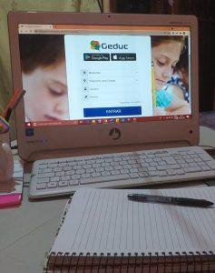 Caderno em frente a tela de computador com a página de abertura da plataforma Geduc.